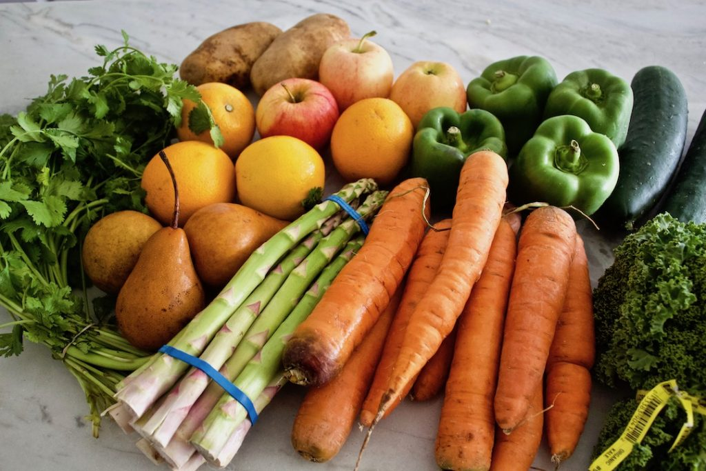 how to eat sustainably: fresh fruits and vegetables on a counter