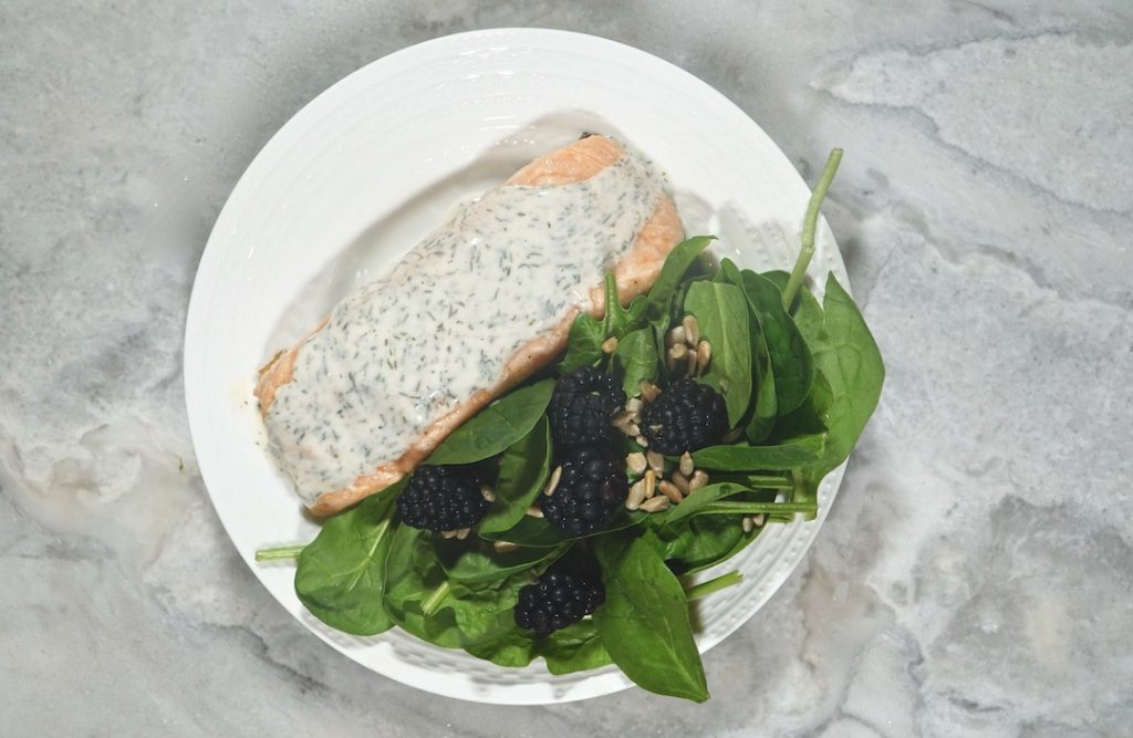 dill yogurt salmon sits on a small dinner plate with a spinach blackberry side salad