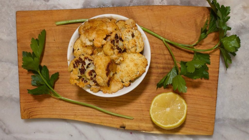 roasted cauliflower on a wooden cutting board with fresh parsley and sliced lemon