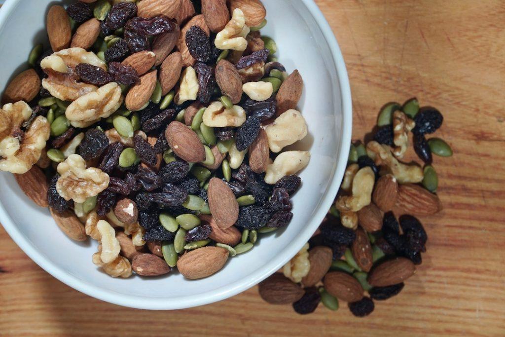 a bowl of homemade trail mix: almonds, walnuts, pumpkin seeds, raisins