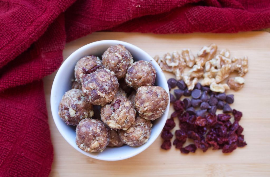 chocolate cherry energy bites with walnuts in a bowl on a wooden cutting board with a red cloth