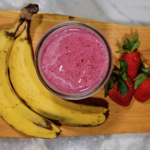 Banana Berry Kefir Smoothie next to two ripe bananas and three fresh strawberries on a wooden cutting board