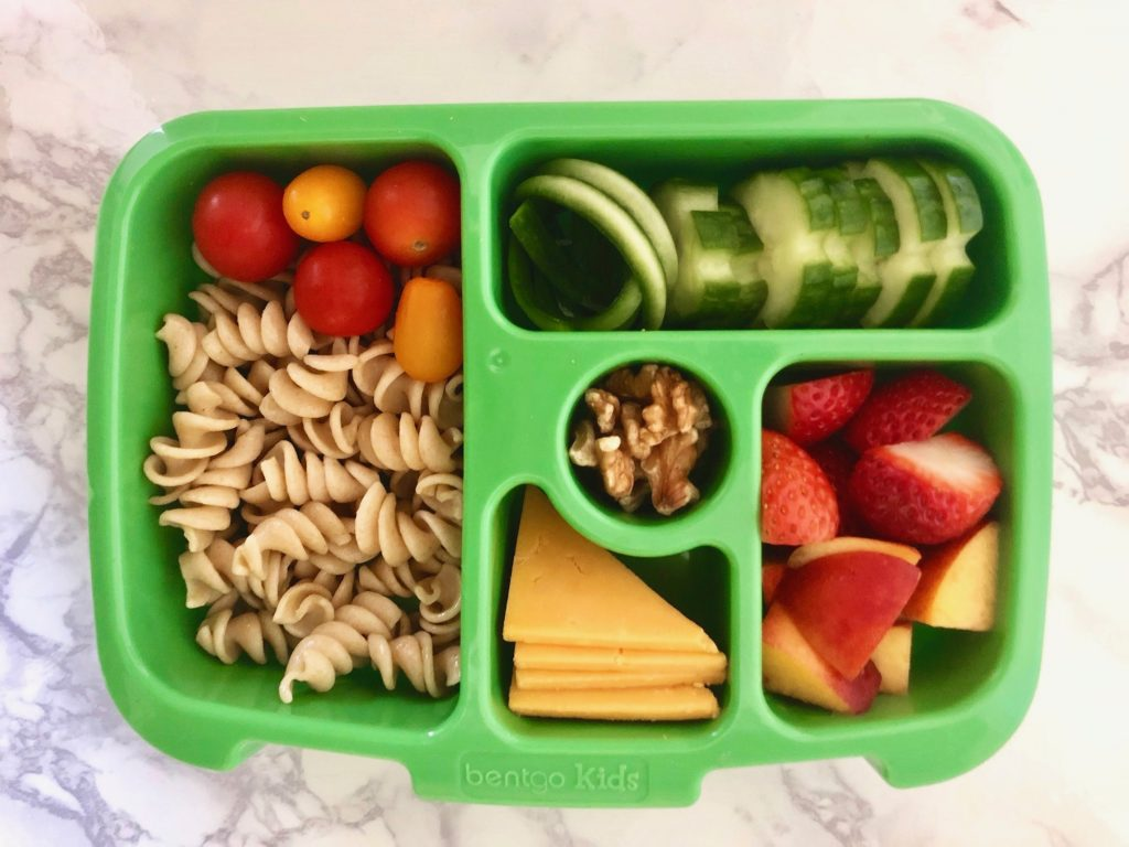 green bentgo kids lunchbox with whole wheat pasta, fresh fruit, sliced cheese, fresh vegetables, cherry tomatoes, and walnuts