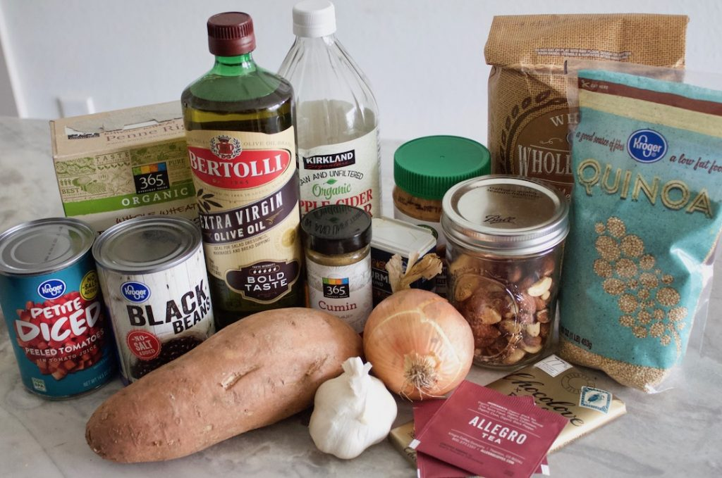 Healthy pantry staples on a counter: nuts, oil, whole grains, chocolate, tea, vegetables, beans, tomatoes, pasta, nut butter, spices, vinegar