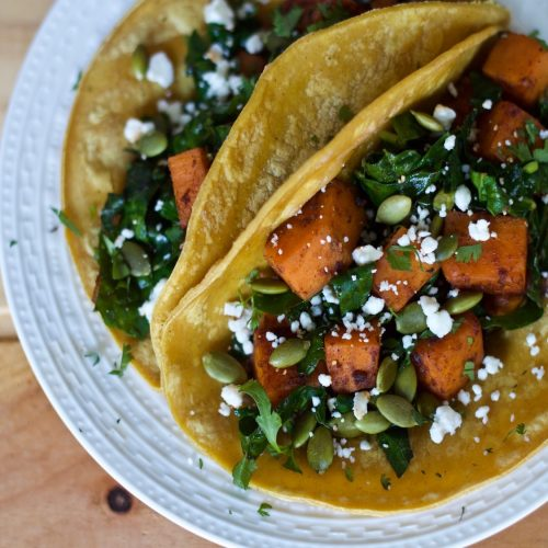 sweet potato kale tacos on a white plate topped with pumpkin seeds and feta cheese