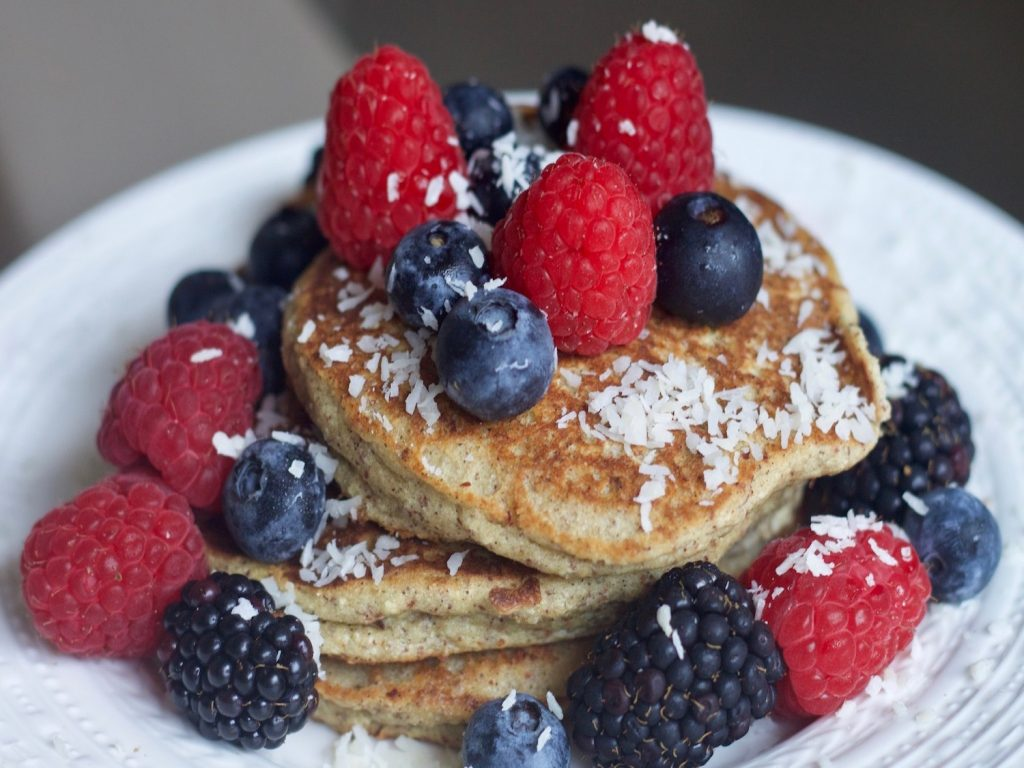 three whole wheat pancakes topped with fresh coconut and fresh berries