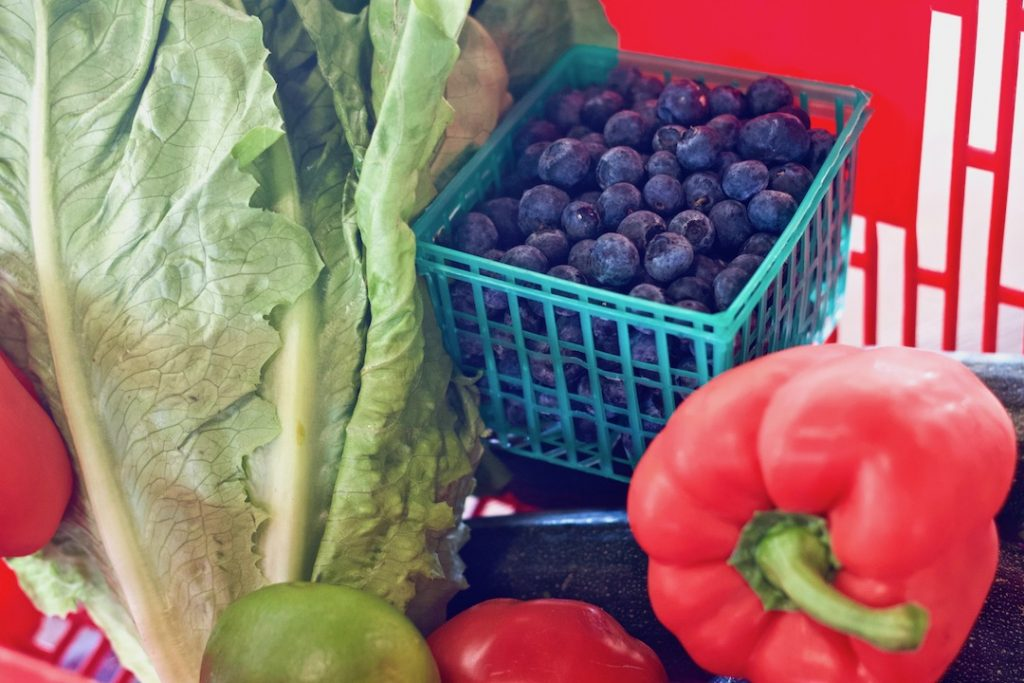 Healthy grocery basket filled with lettuce, blueberries, red bell peppers, and a lime