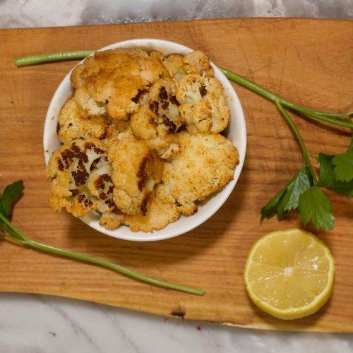 roasted cauliflower on a cutting board with fresh parsley and sliced lemon