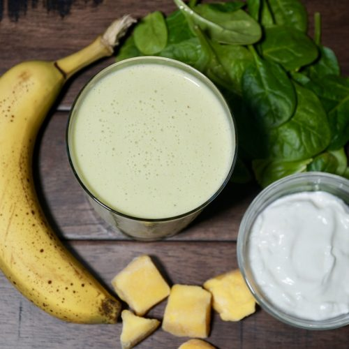 Greek Yogurt Smoothie in cup surrounded by frozen mango, banana, Greek yogurt, and spinach leaves