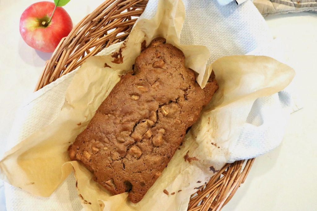 apple cinnamon bread loaf in a basket with fresh apple