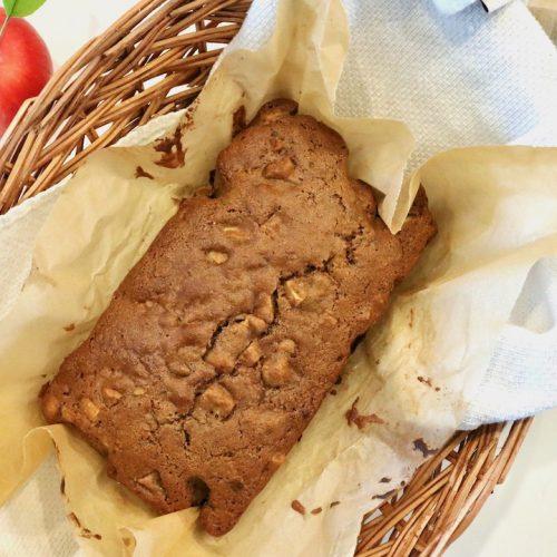 apple cinnamon bread loaf in a basket with fresh apple