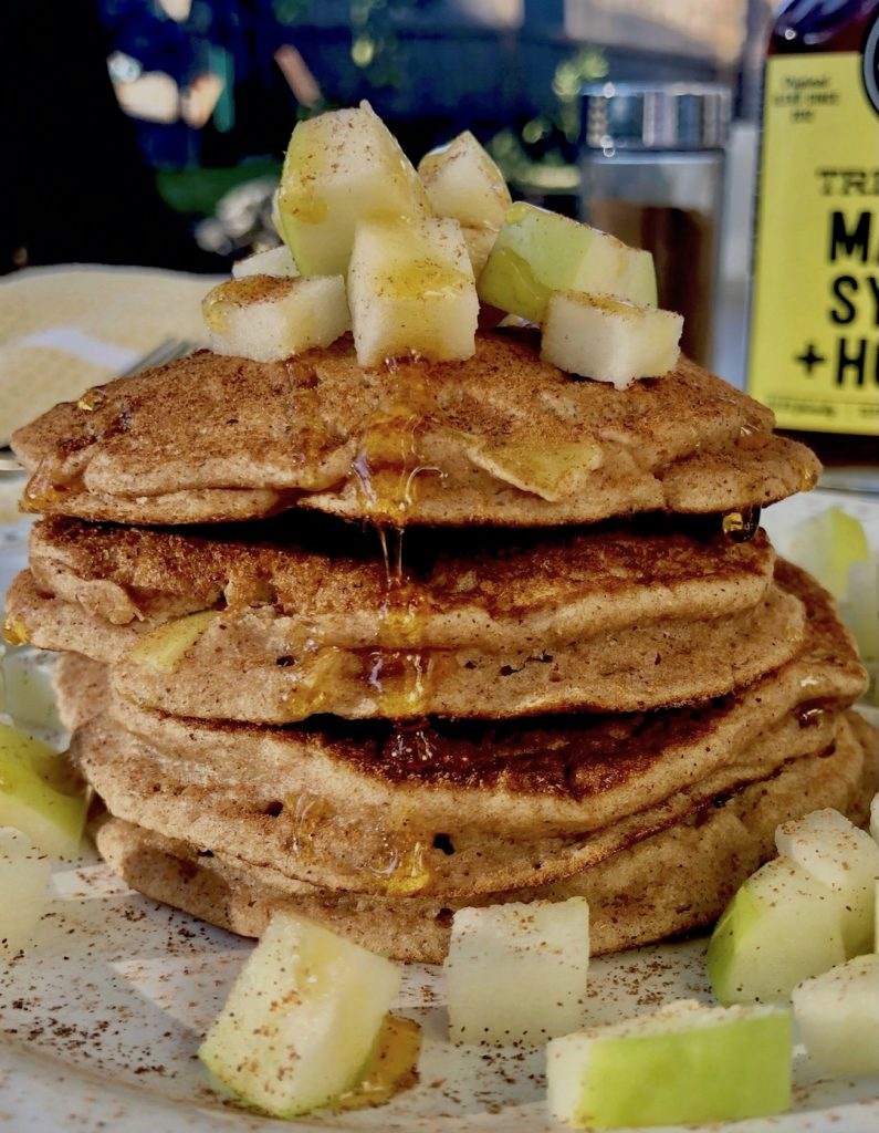 Healthy Apple Pancakes stacked on a plate with fresh apples and syrup.