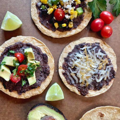 baked tostadas base recipe with variations, avocado, tomato, and cilantro