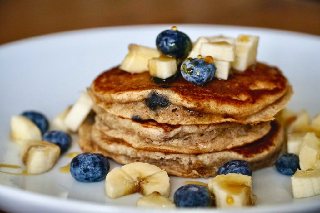 stack of banana blueberry pancakes with fresh blueberries and bananas