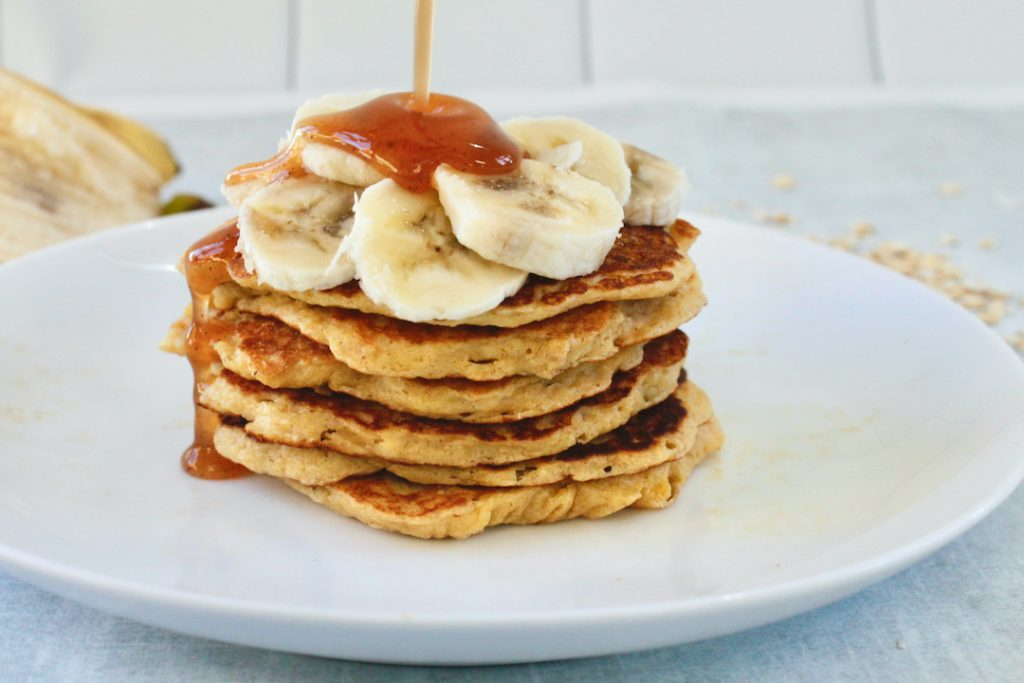 banana oat pancakes with syrup on a table