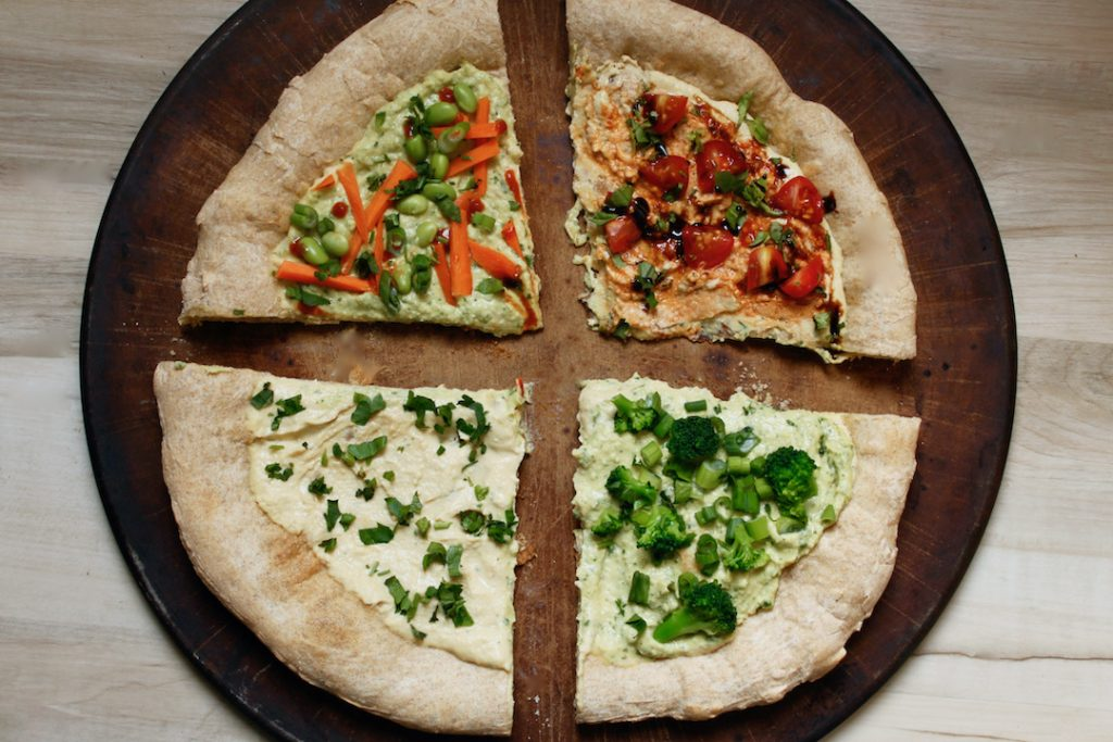hummus pizza base recipe divided into 4 slices