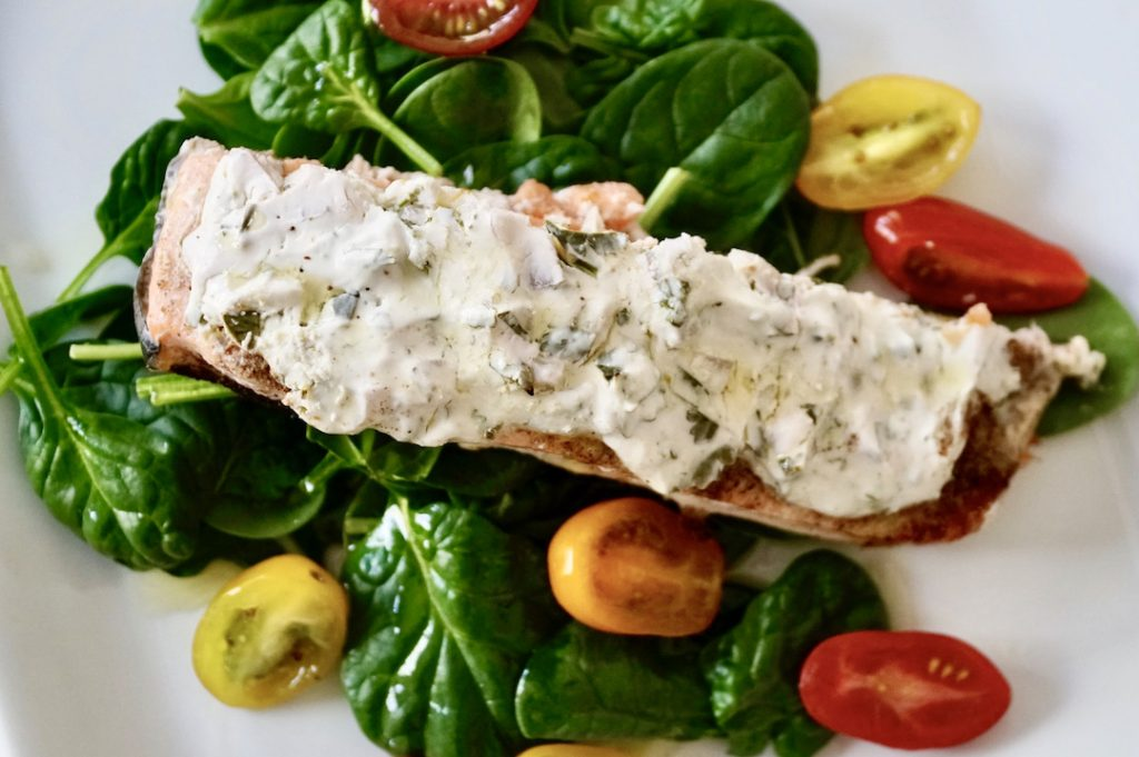 indian spiced salmon on a bed of greens and tomatoes