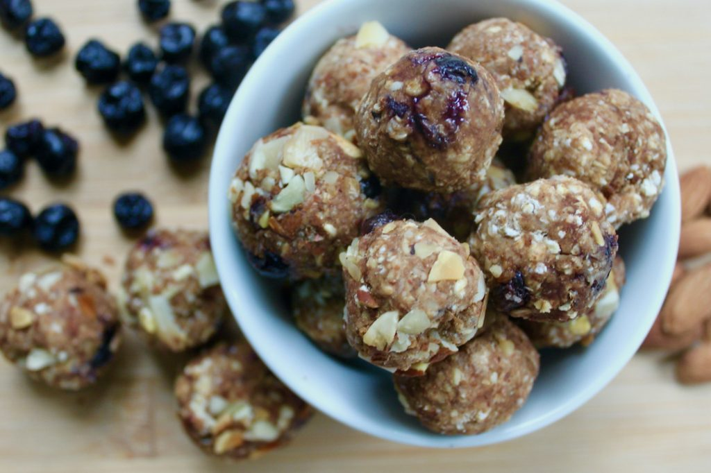 blueberry vanilla energy bites in a bowl with dried blueberries and almonds on the counter