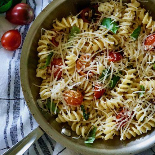 cherry tomato pasta with fresh basil in a medium silver pot