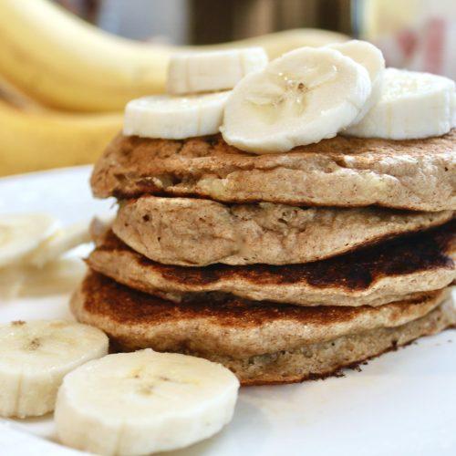 a stack of vegan spelt pancakes with fresh bananas